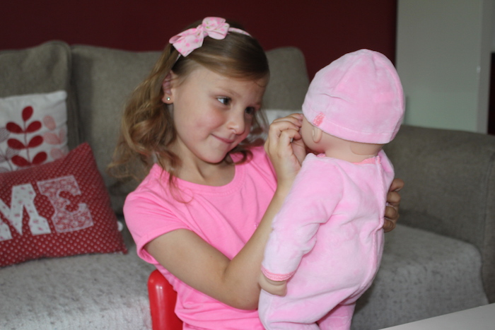 Bella stroking Baby Annabell's cheek