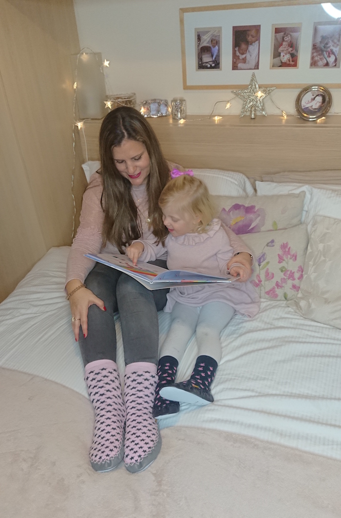 Mummy & daughter having a cosy time wearing a pair of Quality Hand-Sewn Scandinavia Moccis and reading a book