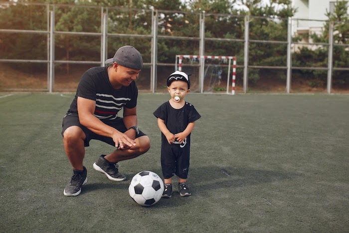 father and son standing on a soccer field