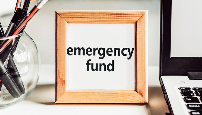 """""""Emergency fund"""" text in a wooden frame on an office table. Financial concept."""