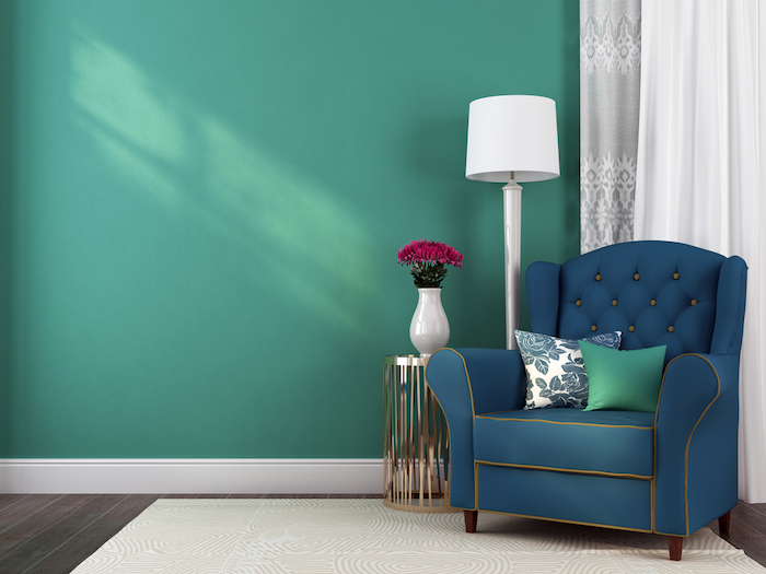 The classic blue armchair, a small table and lamp against a blue wall