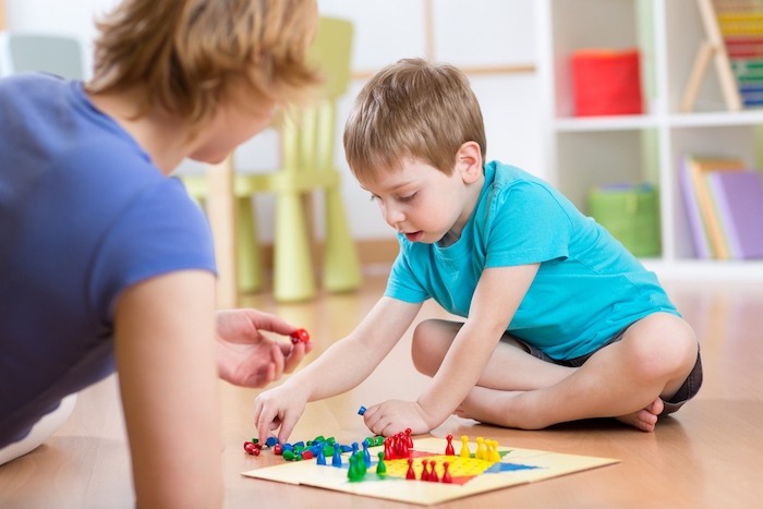 Mother and her son playing in board game on floor in nursery