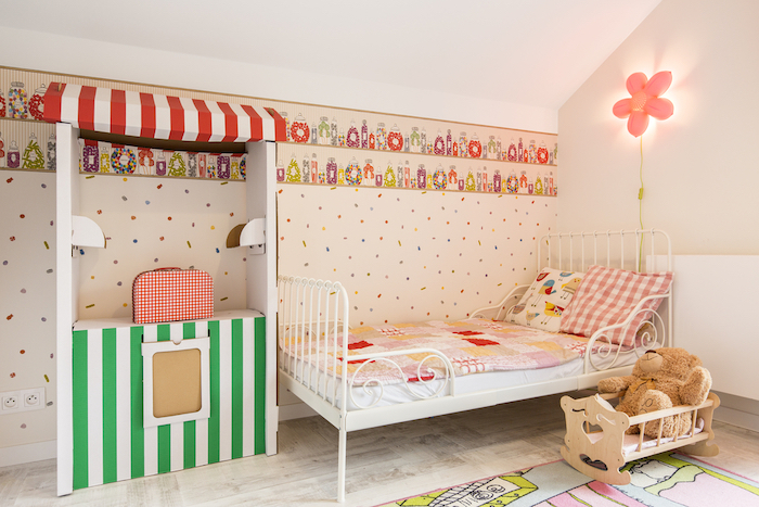 Cozy room designed for little girl. By the wall single bed and paper little house for play